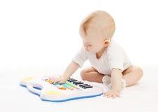 Het nieuwsgierige baby spelen met stuk speelgoed piano Stock Afbeeldingen