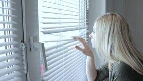Het nieuwsgierige jonge vrouw spioneren, die door de zonneblinden in haar huis gluren stock footage