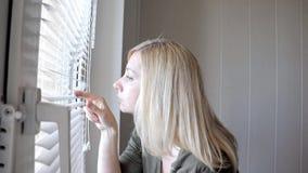 Het nieuwsgierige jonge vrouw spioneren, die door de zonneblinden in haar huis gluren stock videobeelden