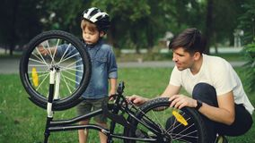 Het nieuwsgierige kind die helm dragen spint fietswiel en pedalen terwijl zijn vader aan hem op gazon in park spreekt stock footage