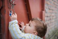Het nieuwsgierige kind spelen met sleutels in openlucht stock foto