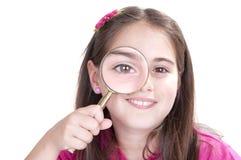 Het nieuwsgierige meisje kijkt door vergrootglas royalty-vrije stock afbeeldingen