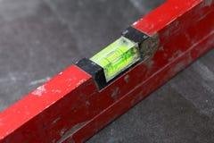 Het niveau die van de bouw thuis de kleefstof van de tegelvloer betegelen stock fotografie