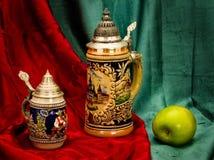 Het nog-leven met biermokken en een groene appel. Stock Fotografie
