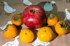 Het nog-leven van de keuken Gezonde rijpe vruchten van granaatappel, mandarine en dadelpruim op een leuk tafelkleed royalty-vrije stock afbeelding