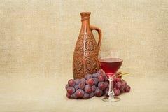 Het nog-leven van een kleifles, druiven en wijn stock afbeeldingen
