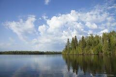 Het noordelijke meer van Minnesota met bomen langs de kust en heldere wolken op een kalme ochtend royalty-vrije stock fotografie