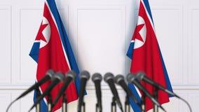 Het noorden Koreaanse officiële persconferentie Vlaggen van Noord-Korea en microfoons Het conceptuele 3d teruggeven Royalty-vrije Stock Afbeeldingen