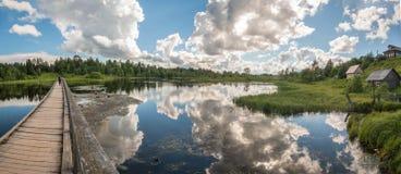 Het noorden Russisch dorp Isady De zomerdag, Emca-rivier, oude plattelandshuisjes op de kust, oude houten brug en wolkenbezinning royalty-vrije stock foto