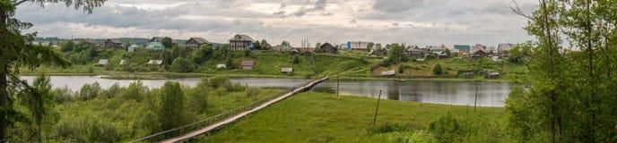 Het noorden Russisch dorp Isady De zomerdag, Emca-rivier, oude plattelandshuisjes op de kust, oude houten brug en wolkenbezinning stock afbeelding