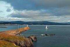 Het Noordenhaven Pier Breakwater Jetty Wall van Wicklow Ierland en Vuurtoren met zeilboot Stock Afbeelding