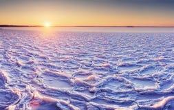 Het Noordpool koude landschap van ijzig meer bij zonsondergang met weefselbarsten en patronen op het ijs stock afbeelding