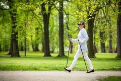 Het noordse lopen - midden-leeftijdsvrouw het uitwerken stock foto's