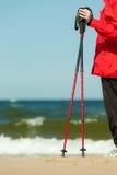 Het noordse lopen Rode stokken op het zandige strand Stock Foto
