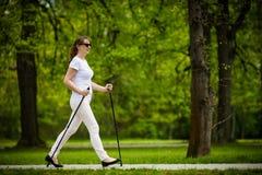 Het noordse lopen - vrouw uitwerken het op middelbare leeftijd royalty-vrije stock fotografie