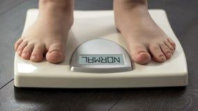 Het normale gewicht, vrouw status op schalen om dieet te controleren vloeit, vooraanzicht voort stock foto's