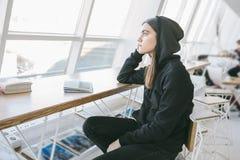 Het nostalgische kijken zorgvuldig uit het venster Het meisje in de heldere winkel van de stadskoffie Zwart-witte kleuren teens stock afbeeldingen
