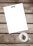 Het notadocument gezet op een oude lijst van de grunge houten textuur met een kop hete koffie, hoogste mening, ruimte voor voegt  Royalty-vrije Stock Foto