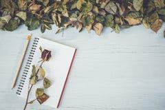 Het notitieboekje en droog nam bloem op wit houten dek met leeg kuuroord toe Royalty-vrije Stock Foto's