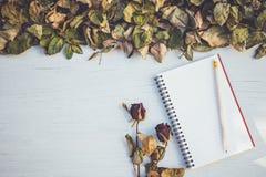 Het notitieboekje en droog nam bloem op wit houten dek met leeg kuuroord toe Royalty-vrije Stock Fotografie