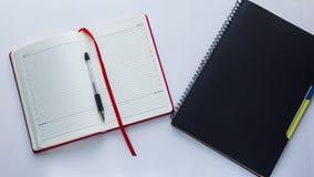 Het notitieboekje en een pen zijn op de lijst Stock Foto