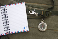 Het notitieboekje en het kompas met veiligheid haken op riem van een rugzak vast Royalty-vrije Stock Afbeeldingen
