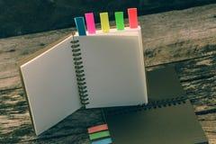 Het notitieboekje met het lusje van de kleurennota op houten lijst voor voegt tekstmessa toe royalty-vrije stock afbeeldingen