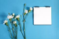 Het notitieboekje op de lentes met een wit nam op een blauwe achtergrond met een lege ruimte voor nota's toe Royalty-vrije Stock Foto