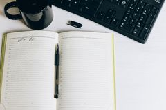 Het notitieboekje op de lijst met pen en mok royalty-vrije stock afbeelding