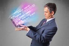 Het notitieboekje van de zakenmanholding met exploderende gegevens en aantallen Stock Fotografie