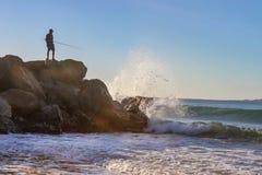 Het oceaanwater spashing tegen de rotsen en omhoog in de lucht als visser bevindt zich in sihloutte bovenop de dagzomende aardlaa Royalty-vrije Stock Afbeelding