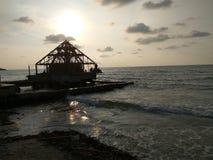 Het oceaanwater van het zonsondergangstrand met de unfinishbouw Stock Afbeelding