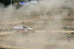 Het off-road voertuig kruist de hoek en brengt omhoog rook en stof Stock Fotografie