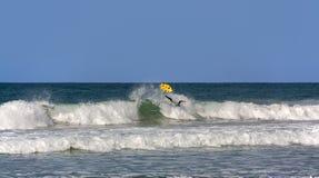 Het ogenblik valt de surfer van de raad stock foto's