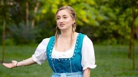 Het Oktoberfestmeisje nodigt mensen aan het festival uit stock video
