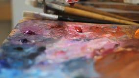 Het olieverfschilderij van de de mengelingskleur van de kunstenaarsborstel op palet houdt in zijn handclose-up de kunstenaarsduwe stock footage