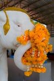 Het olifants` s beeldhouwwerk is verfraaid met oranje bloemen Stock Foto's