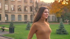 Het omcirkelen rond mening van het mooie donkerbruine meisje lopen langs herfstpark met glimlach stock footage