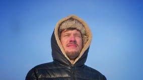 Het omcirkelen rond mening van ontdekkingsreiziger op middelbare leeftijd in kap het letten zorgvuldig op op de omgeving op sneeu stock footage