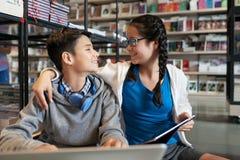 Het omhelzen van gelukkige tieners in bibliotheek royalty-vrije stock fotografie