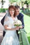 Het omhelzen van huwelijkspaar bij de zomer Stock Foto