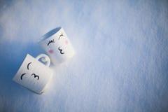 Het omhelzen van twee mokken met een beeld in de sneeuw Stock Fotografie