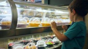 Het onafhankelijke jonge geitje kiest maaltijd in koffie, kijkt de jongen dichtbij showcase op transportbandlijn met het bewegen  stock videobeelden