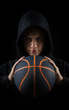 Het onbeschofte basketbal met een kap van de jongensholding Royalty-vrije Stock Afbeeldingen