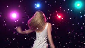 Het onbezorgde meisje danst en wervelt tegen lichten Langzame Motie stock videobeelden