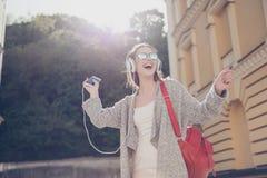 Het onbezorgde meisje luistert aan favoriet lied en danst buiten royalty-vrije stock foto