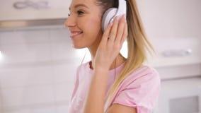 Het onbezorgde vrouw dansen die aan muziek thuis keuken luisteren in langzame motie stock videobeelden
