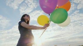 Het onbezorgde zwangere vrouw spelen met ballons in een weide, tegen een blauwe hemelachtergrond stock videobeelden