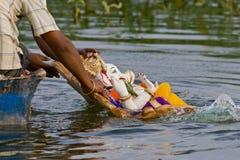 Het onderdompelen van LordGanesha idool in de rivier Stock Foto's