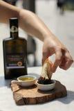 Het onderdompelen van Vers Italiaans Brood in Balsemieke Azijn Stock Foto's